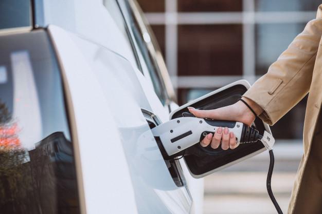 Frau betankt Elektroauto